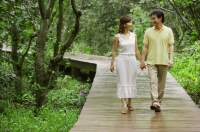 Mature couple walking on path in park, holding hands - Alex Mares-Manton