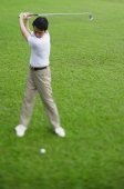 Man swinging golf club, selective focus - Alex Mares-Manton
