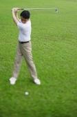 Man swinging golf club, selective focus - Alex Mares-Manton