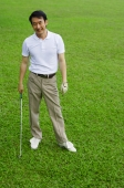 Man standing on golf course, holding golf club, smiling - Alex Mares-Manton
