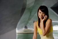 Woman using mobile phone, smiling - Yukmin