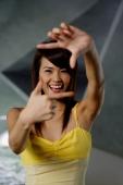 Woman looking through finger frame - Yukmin