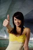 Woman making thumbs-up sign, smiling - Yukmin