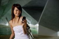 Woman in white tube top using mobile phone, text messaging - Yukmin