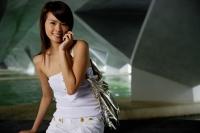 Woman in white tube top using mobile phone - Yukmin