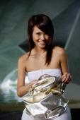 Woman in white tube top holding bag, smiling at camera - Yukmin