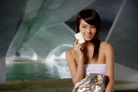 Woman in white tube top holding credit card against face - Yukmin