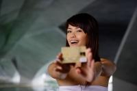 Woman in white tube top holding credit card towards camera - Yukmin