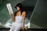 Woman reading newspaper, coffee cup next to her - Yukmin
