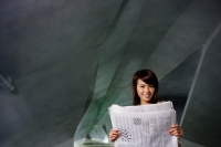 Woman in tunnel, holding newspaper, smiling at camera - Yukmin