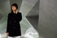 Woman in black jacket, using mobile phone, looking away - Yukmin