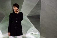 Woman in black jacket, using mobile phone, smiling - Yukmin