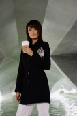 Woman in black jacket, holding disposable coffee cup and newspaper - Yukmin