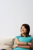 Woman sitting on sofa, hugging cushion, looking away - Nugene Chiang