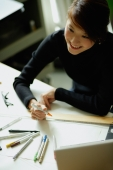 Female designer sitting at table with ruler and felt tip marker - Nugene Chiang
