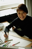 Female designer sitting at table with ruler and felt tip marker, smiling at camera - Nugene Chiang