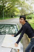 Woman with map spread out on hood of car, looking at camera - Alex Mares-Manton