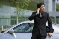 Businessman using mobile phone, leaning on car - Alex Mares-Manton