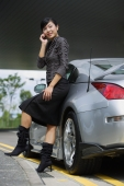 Woman leaning on car, using mobile phone - Alex Mares-Manton