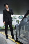 Businessman with hand on chin, looking at car - Alex Mares-Manton