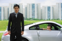 Businessman standing next to sports car, woman in car, looking out the car window - Alex Mares-Manton