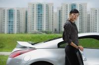 Woman getting into silver sports car, looking at camera - Alex Mares-Manton