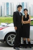 Couple standing side by side, silver sports car behind them - Alex Mares-Manton