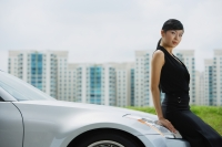 Woman leaning on hood of car, looking at camera - Alex Mares-Manton