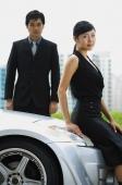 Woman sitting on car hood, man standing behind her - Alex Mares-Manton