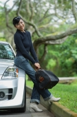 Woman holding bag, leaning on car, smiling at camera - Alex Mares-Manton