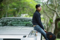 Woman holding bag, sitting on hood of car - Alex Mares-Manton