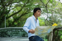 Man sitting on hood of car, holding map, looking away - Alex Mares-Manton
