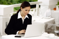 Businesswoman sitting in restaurant, using laptop - Yukmin