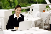 Businesswoman sitting in restaurant with laptop, looking at camera - Yukmin