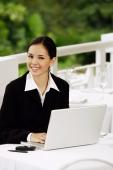 Businesswoman sitting with laptop, looking at camera - Yukmin