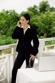 Businesswoman standing, using mobile phone - Yukmin