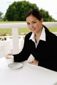 Businesswoman sitting in cafe, having coffee, looking at camera - Yukmin