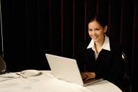 Businesswoman sitting in restaurant using laptop, smiling - Yukmin