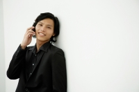 Businessman leaning on wall, using mobile phone, smiling - Yukmin