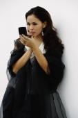 Woman wearing black shawl, looking at compact - Yukmin