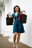 Young woman holding shopping bags, smiling - Yukmin