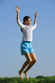 Girl jumping in mid air, smiling at camera - Alex Mares-Manton