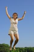 Woman jumping in mid air, smiling at camera - Alex Mares-Manton