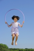Girl in lavender dress, jumping in mid air, holding hoop - Alex Mares-Manton