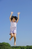 Girl jumping in mid air, arms outstretched, smiling - Alex Mares-Manton