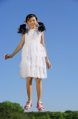 Girl wearing white dress, jumping in mid air, smiling at camera - Alex Mares-Manton
