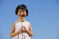 Girl with multi-coloured lollipop, portrait - Alex Mares-Manton