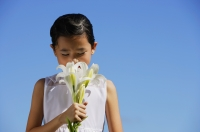 Girl smelling bouquet of flowers - Alex Mares-Manton