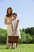 Mother and daughter in park, looking at camera, girl holding picnic basket - Alex Mares-Manton