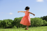 Girl in peach dress, walking on grass, arms outstretched - Alex Mares-Manton